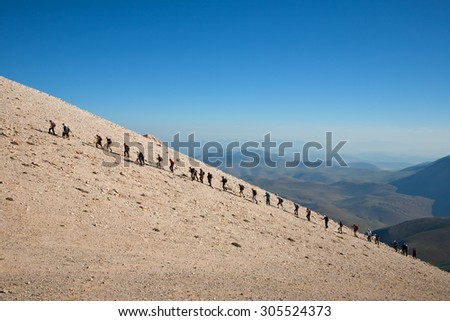 Group of climbers sportsmen hiking to the mountain peak with blue sky background - stock photo