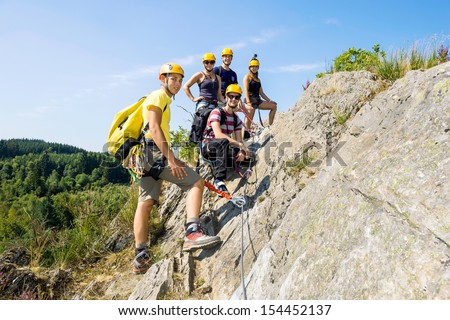 Group of climbers with safety equipment on rock - stock photo