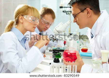 Group of clinicians experimenting with new substance in laboratory - stock photo