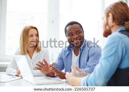 Group of co-workers in casual interacting at business meeting - stock photo
