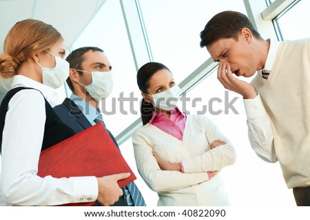 Group of co-workers in protective masks looking strictly at sneezing man - stock photo
