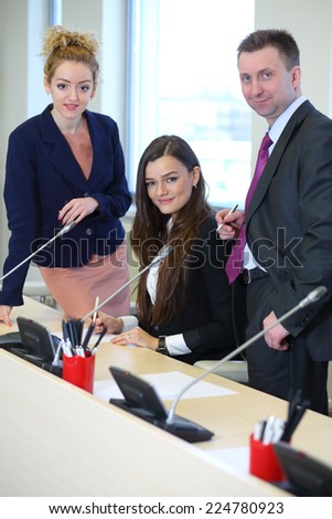 Group of colleagues: businessman and two businesswomen corrects documents in the conference hall - stock photo
