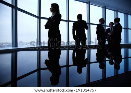 Group of colleagues standing along window in office - stock photo