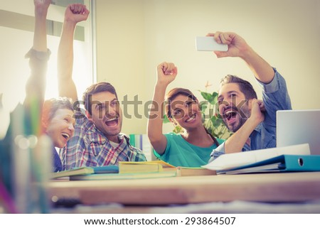 Group of colleagues taking a selfie in the office - stock photo
