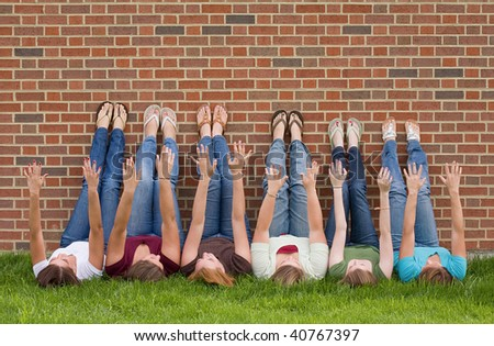 Group of College Girls at School With Legs up on Wall - stock photo