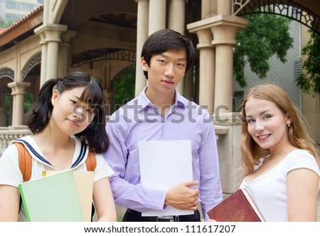 Group of college students holding books. American and Asian teenagers studying outside of university campus - stock photo