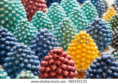 Group of colored ceramic pine cones with a focus on the yellow one in a pottery workshop of Caltagirone - stock photo