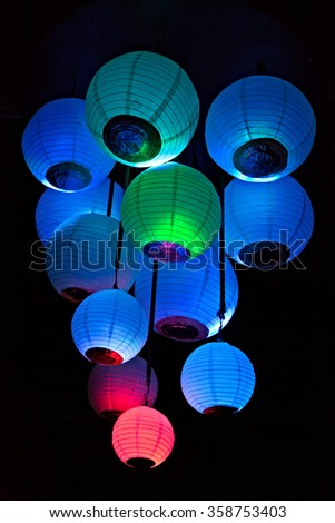 Group of colored paper lanterns glowing in the dark - stock photo