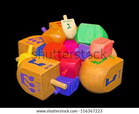 Group of colorful Chanukah dreidels. Pile of wood and plastic Jewish holiday dreidels isolated on a black background. Mulicolored Hebrew letters gimmel, nun, hey, shin.  - stock photo