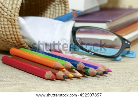 group of colorful  pencil on desk wooden with books and glass,colorful of pin - stock photo