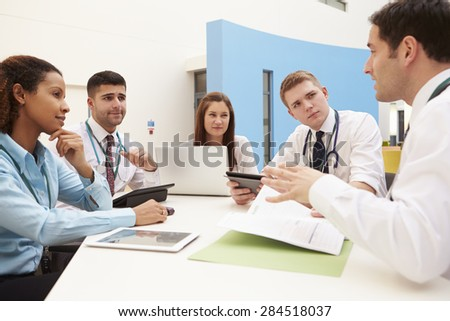 Group Of Consultants Sitting At Table In Hospital Meeting - stock photo