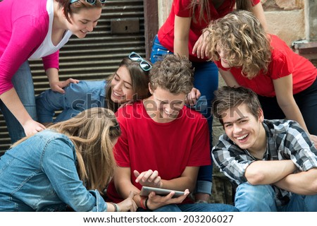 Group of cool teenagers playing with tablet - stock photo
