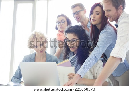 Group of creative businesspeople using laptop in office - stock photo