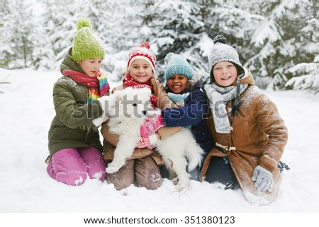 Group of cute children and their dog in winter park - stock photo