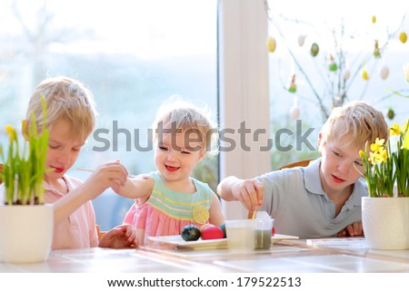 Group of cute children from one family, two twin brothers and their little toddler sister, decorating and painting Easter eggs sitting together in the kitchen on a sunny day. Selective focus on girl. - stock photo