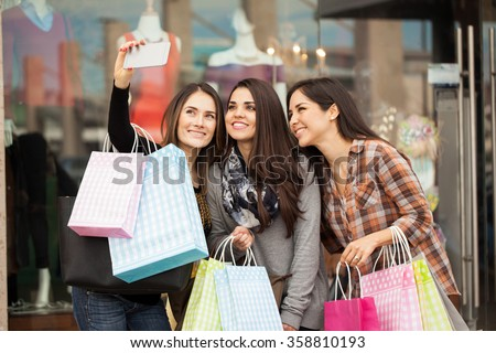 Group of cute female friends doing some shopping at a mall and taking a selfie with a smartphone - stock photo
