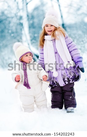 group of cute happy children walking in winter snow park. Two little girl in warm fashion clothes.  - stock photo