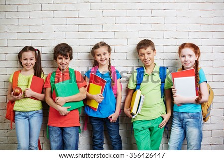 Group of cute schoolkids standing by wall and looking at camera - stock photo