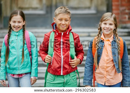 Group of cute schoolmates with backpacks looking at camera - stock photo