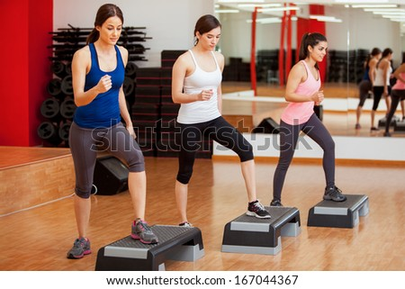 Group of cute women working out and doing some step aerobics - stock photo