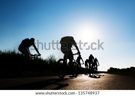 group of cyclists biking in motion - stock photo