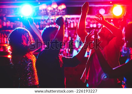 Group of dance lovers enjoying disco in nightclub - stock photo