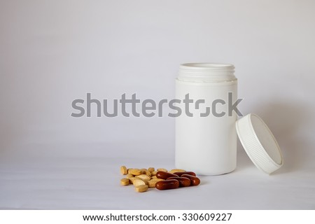 Group of different pills and white bottle multivitamins on a dark background  - stock photo