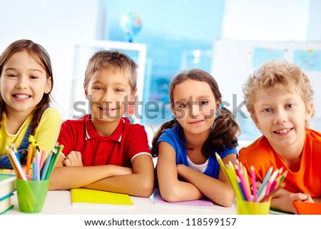 Group of diligent schoolchildren looking at camera in school - stock photo