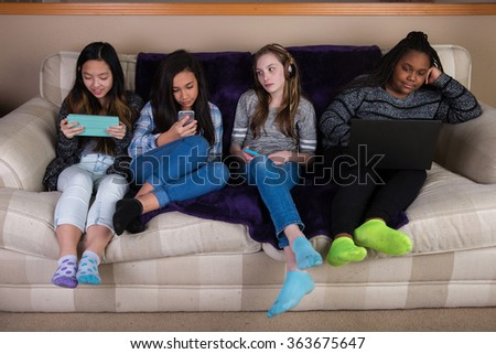 Group of disengaged, bored children on mobile devices - stock photo