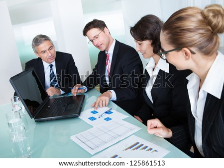 Group of diverse business executives holding a meeting around a table discussing graphs showing statistical analysis - stock photo
