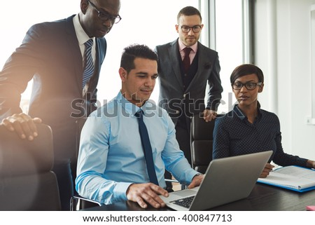 Group of diverse business people in formal clothing inside their office discussing or looking at information on a laptop computer - stock photo