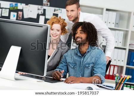 Group of diverse multiethnic business colleagues in the office smiling as they stand looking at a large desktop monitor with intense interest - stock photo