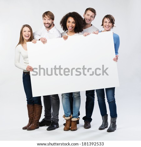 Group of diverse multiethnic happy young people posing with a blank white rectabgular sign with copyspace for your advertisement or text on a grey background - stock photo