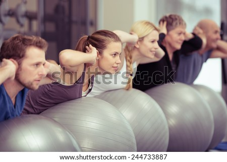 Group of diverse people in a receding line doing pilates in a gym balancing over the gym balls with their hands laocked behind their necks toning their muscles - stock photo