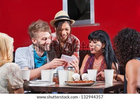 Group of diverse people laughing with phone and eating pizza - stock photo