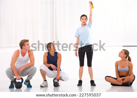Group of diverse people looking woman lifting kettlebell in gym - stock photo