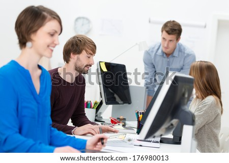 Group of diverse young businesspeople working in a busy office at desktop computers - stock photo