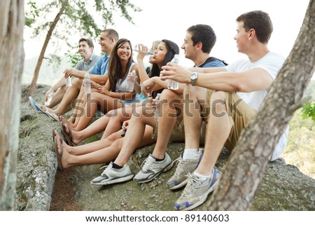 Group of diverse young hikers taking a water break on a cliff at Great Falls National park in Virginia - stock photo