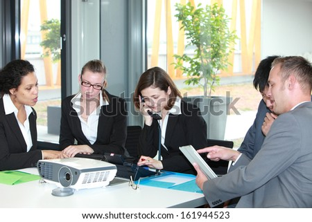 Group of diverse young multiethnic business professionals in a meeting sitting around a table discussing various documents while one woman talks on the telephone - stock photo