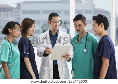 Group of doctors and nurses standing in a hospital. Multi-ethnic team of caucasian, Chinese and indian medical staff. - stock photo