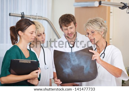 Group of doctors discussing over Xray in hospital - stock photo