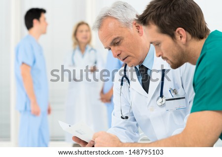 Group Of Doctors Involved In Serious Discussion With Medical Records - stock photo