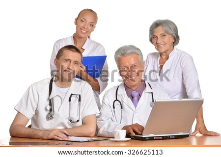 Group of doctors with laptop at the table - stock photo