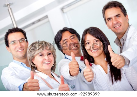 Group of doctors with thumbs up at the hospital - stock photo