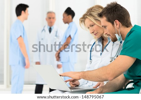Group Of Doctors Working On Laptop In Hospital - stock photo