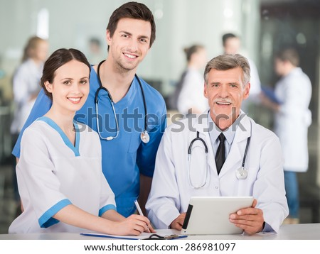 Group of doctors working together on digital tablet at doctor's office. - stock photo