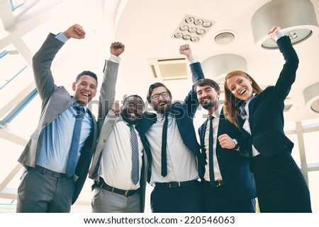 Group of ecstatic business leaders with raised arms expressing their gladness - stock photo