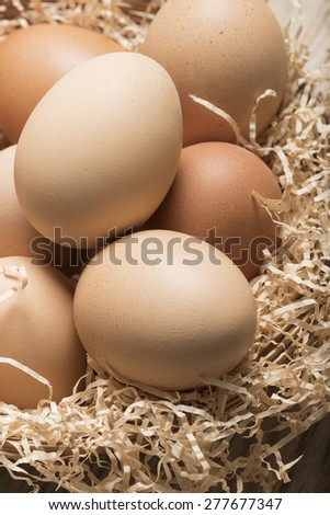 group of eggs in straw basket on wooden table - stock photo