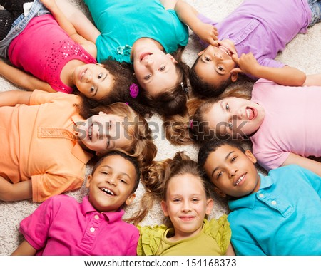 Group of eight happy diversity looking kids, boys and girls laying in star shape on the floor - stock photo