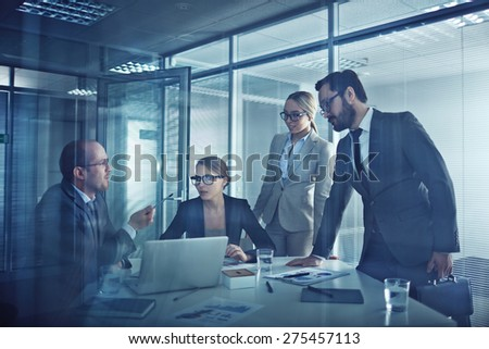 Group of elegant business partners talking at meeting in office - stock photo